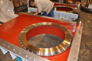 Large machined jet valve components being assembled.
